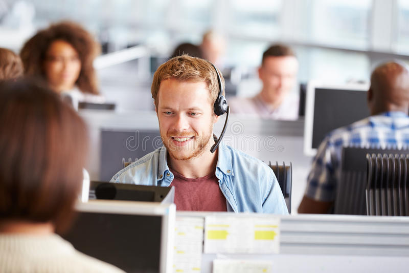 Young man working at a computer in a call centre stock image