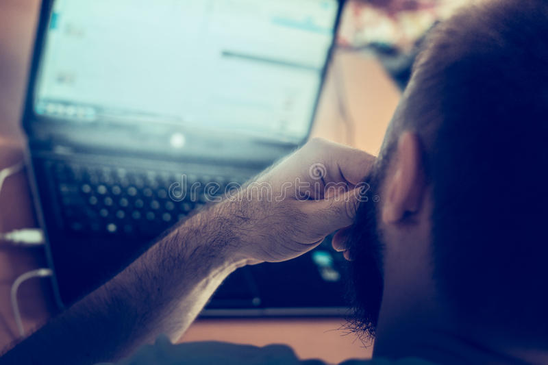 Young man working at a computer, home office, blurred background royalty free stock image