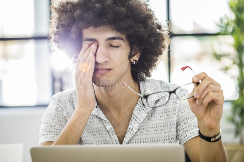 Young man working with computer while rubbing his eye stock photography