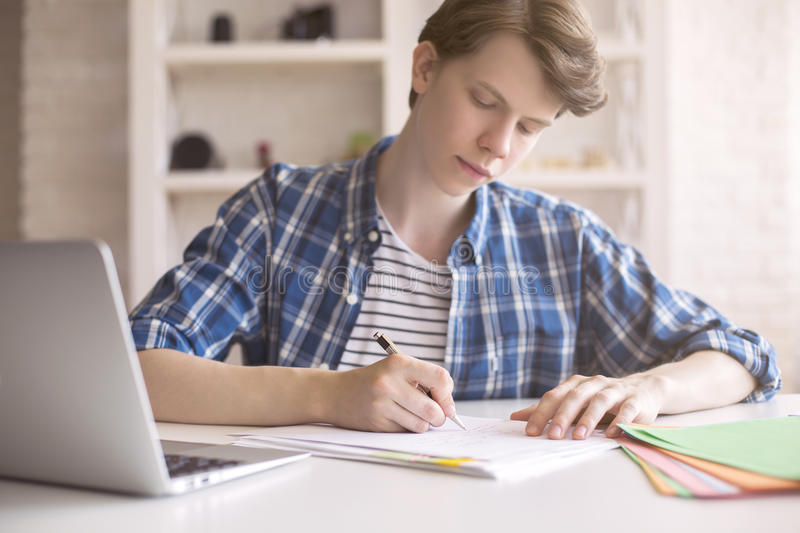 Young man working on coursework royalty free stock photos