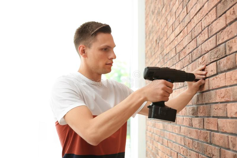 Young man working with electric screwdriver near wall stock images