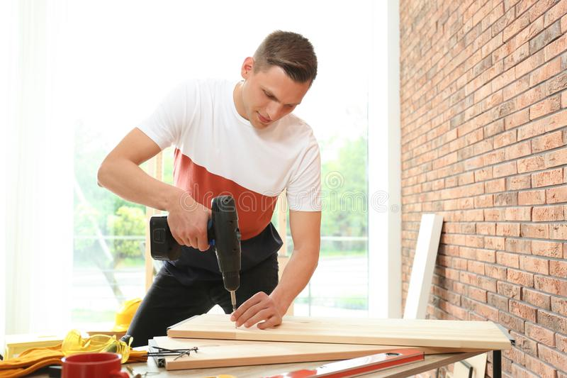 Young man working with electric screwdriver royalty free stock image
