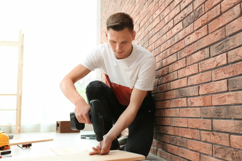 Young man working with electric screwdriver stock image