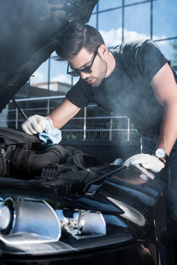 young man in working gloves trying to repair engine of broken car with smoke coming stock photos