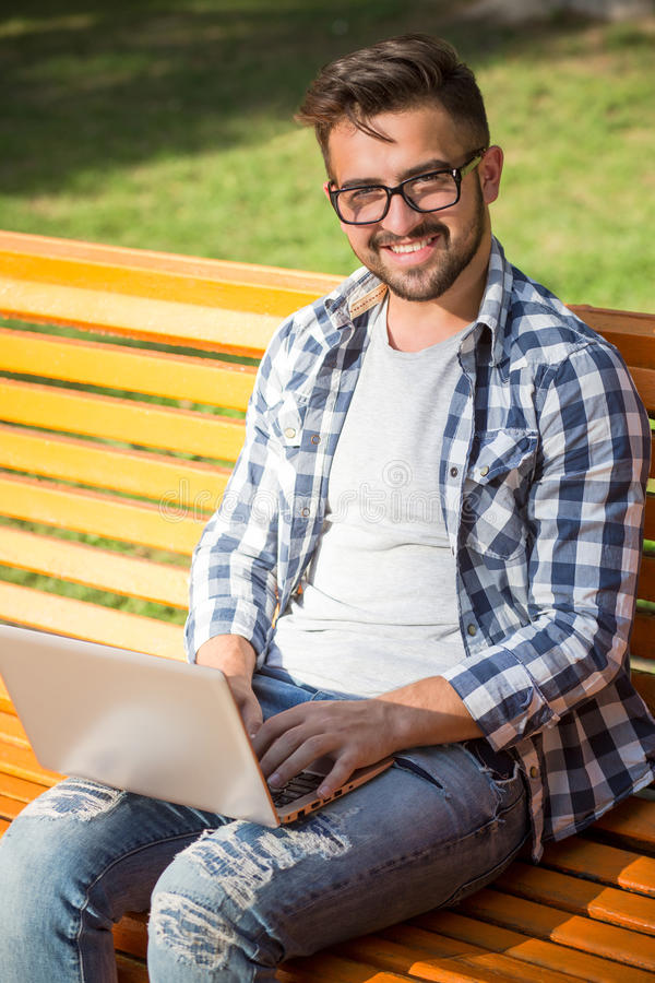 Young man working on his laptop on the bench outdoors stock images