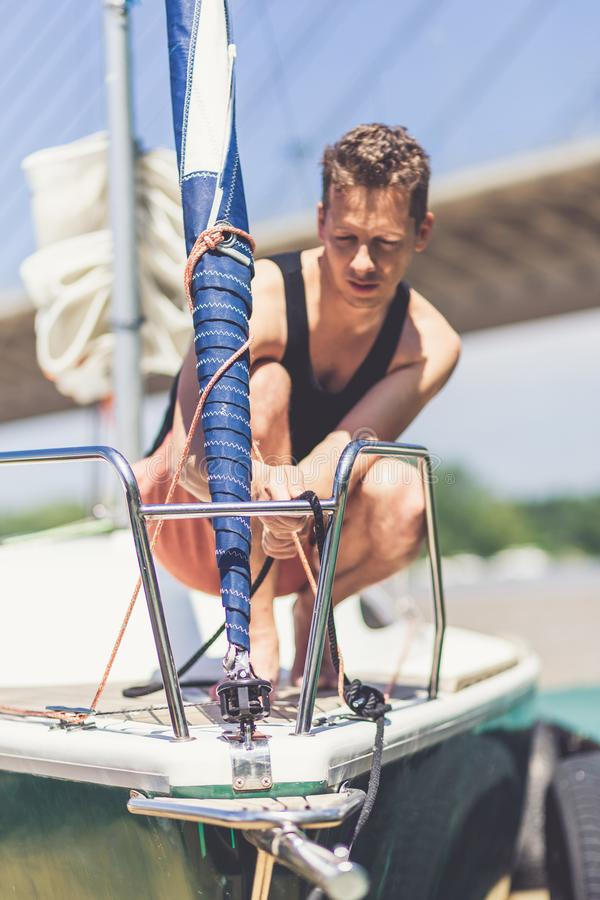 Young man working on his sailboat. Summer and travel concept stock images