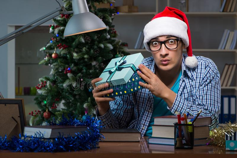 The young man working at home on christmas day. Young man working at home on christmas day stock photography