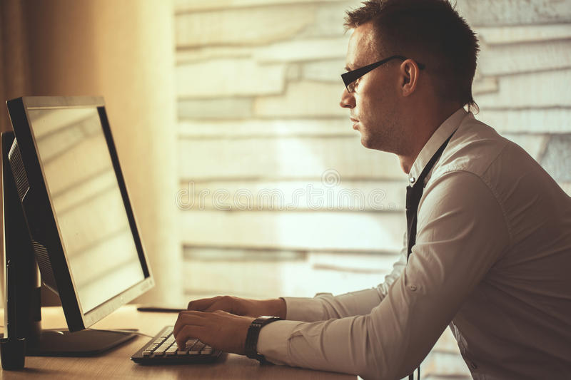 young man working from home on computer, manager at his workplace using technology, flare light.Male hands typing on laptop stock photo