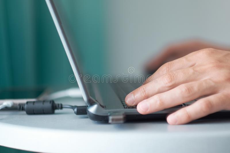 Young man working with laptop, man`s hands on notebook computer, business person at workplace stock photos