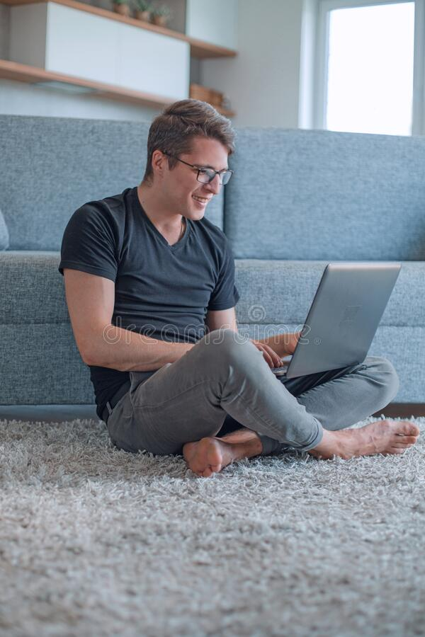 Young man working on laptop sitting on carpet in living room royalty free stock photo