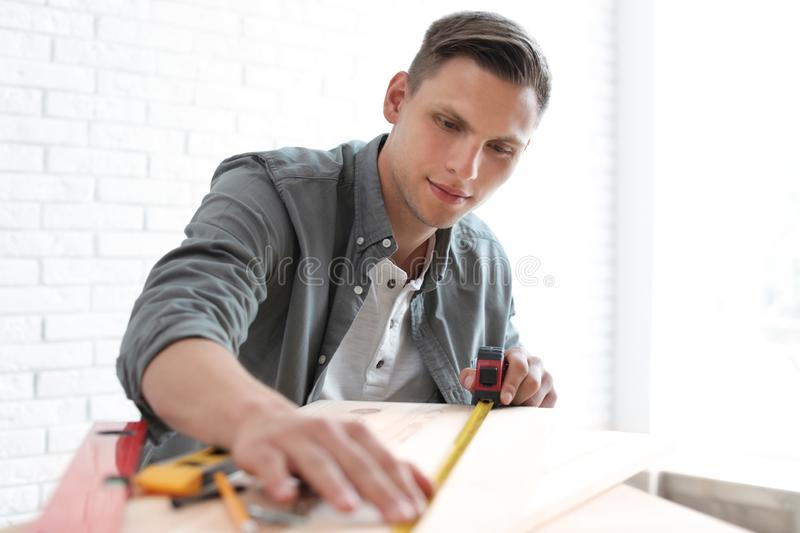 Young man working with measuring tape stock photos