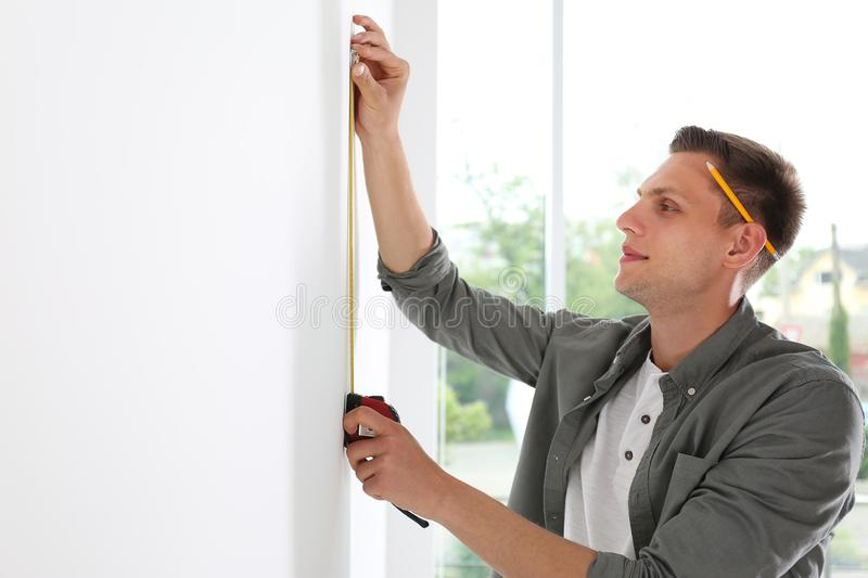 Young man working with measuring tape near white wall stock image