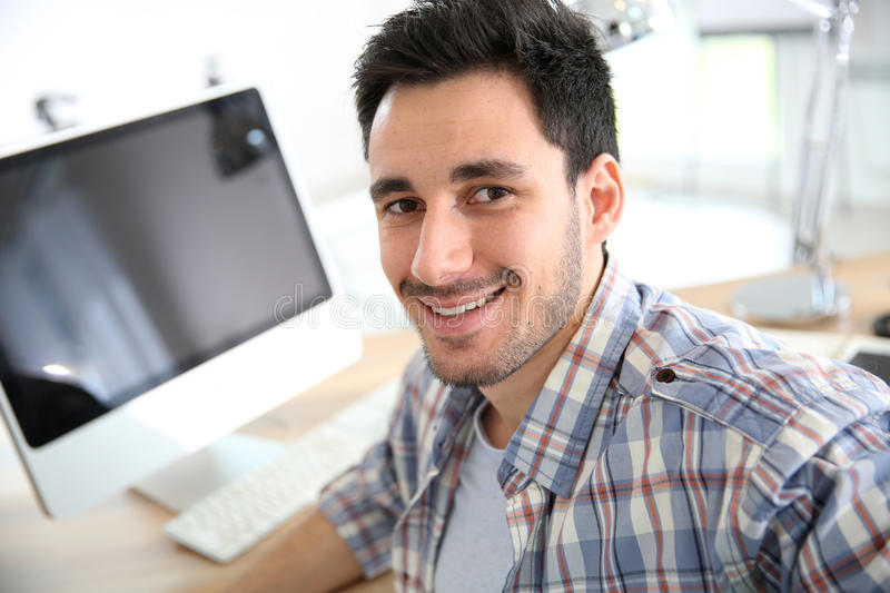 Young man working at office. Smiling young adult in office royalty free stock photography