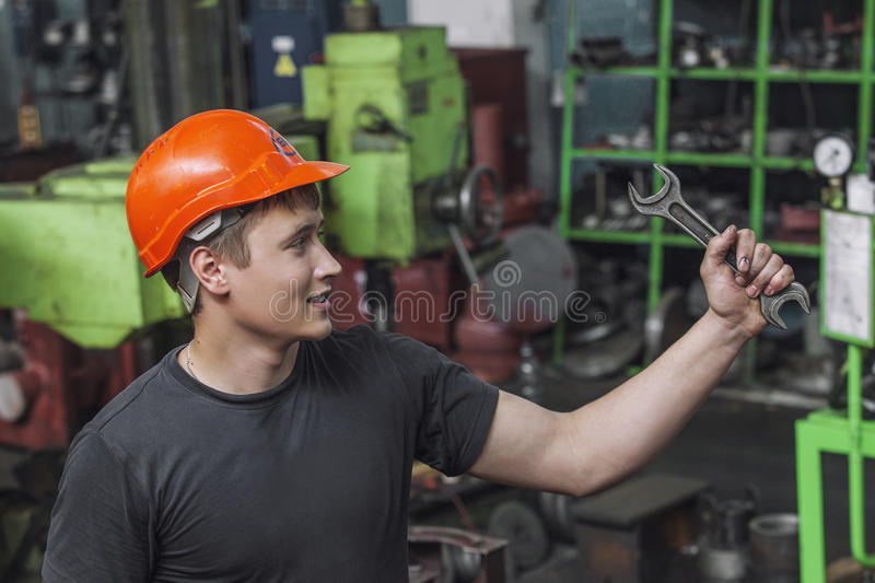 The young man working at the old factory on installation of equipment stock photos