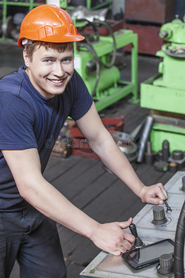 The young man working at the old factory on installation of equipment royalty free stock photos
