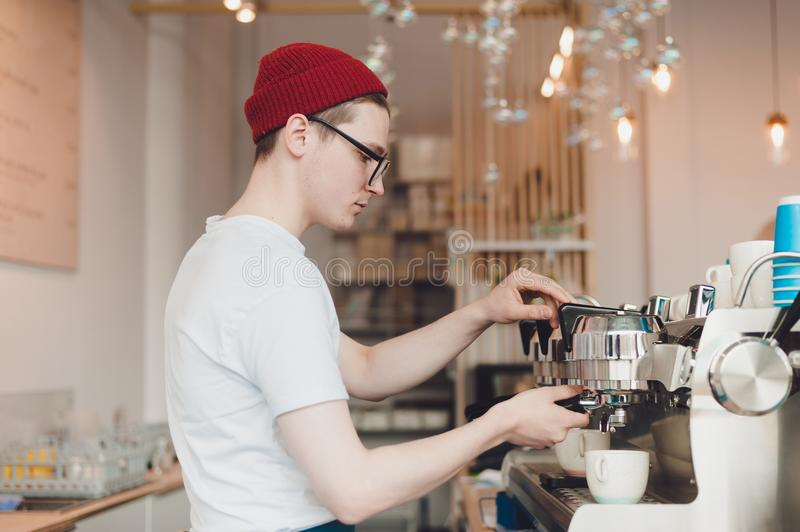 Barista stands behind the coffee machine and makes coffee stock photo