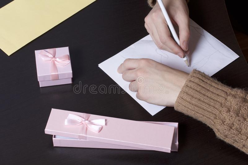 A young man writes holiday greetings on a sheet of paper. Near the box with gifts and an envelope.  stock images