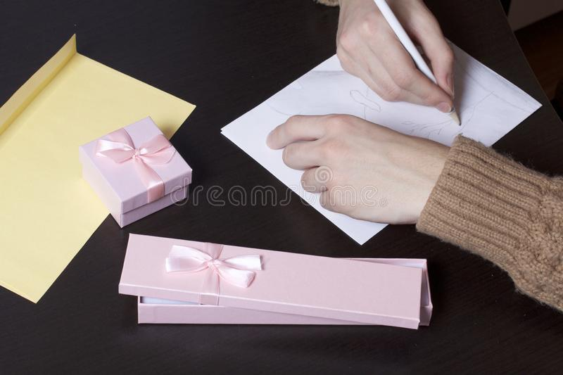 A young man writes holiday greetings on a sheet of paper. Near the box with gifts and an envelope.  stock image