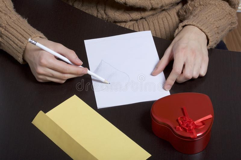 A young man writes holiday greetings on a sheet of paper. Next to the box with a gift and an envelope. Box of tin, red, made in. The shape of a heart stock photos