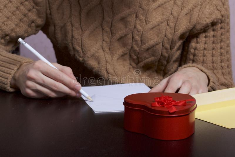 A young man writes holiday greetings on a sheet of paper. Next to the box with a gift and an envelope. Box of tin, red, made in. The shape of a heart stock photo