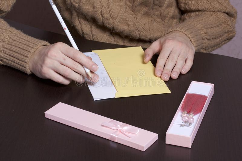 A young man writes holiday greetings on a sheet of paper. Next to the box with a gift and an envelope. In the open box, earrings. Are visible stock image