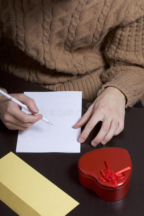 A young man writes holiday greetings on a sheet of paper. Next to the box with a gift and an envelope. Box of tin, red, made in. The shape of a heart royalty free stock photos