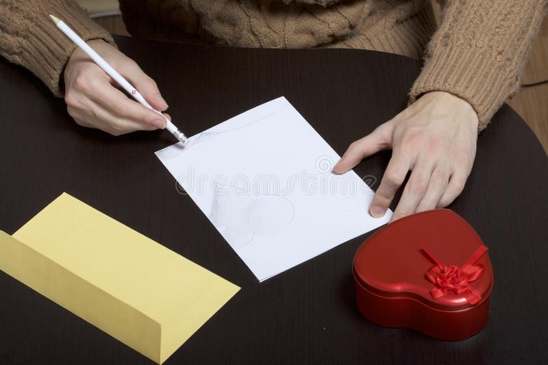 A young man writes holiday greetings on a sheet of paper. Next to the box with a gift and an envelope. Box of tin, red, made in. The shape of a heart stock images