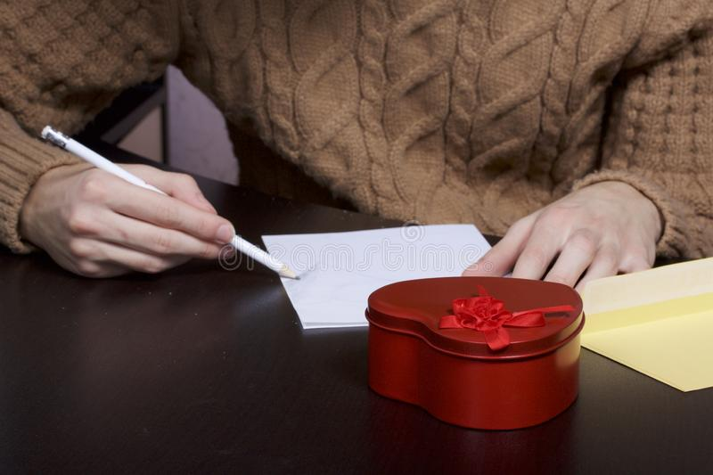 A young man writes holiday greetings on a sheet of paper. Next to the box with a gift and an envelope. Box of tin, red, made in. The shape of a heart royalty free stock image