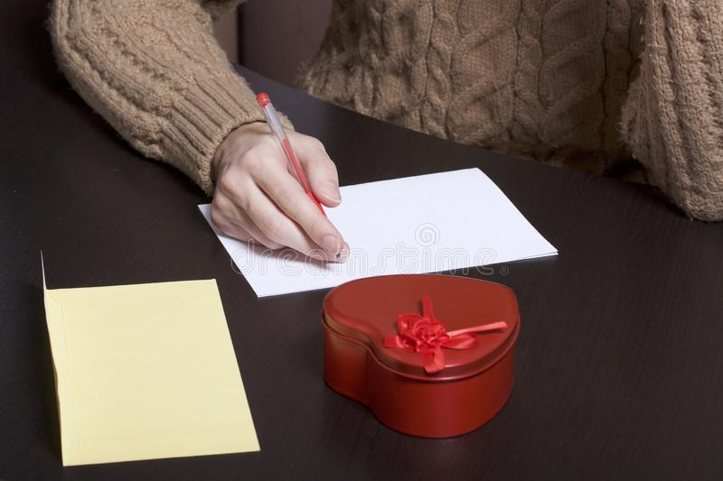A young man writes holiday greetings on a sheet of paper. Next to the box with a gift and an envelope. Box of tin, red, made in. The shape of a heart royalty free stock photography