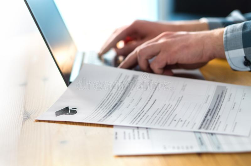 Young man writing college or university application form. royalty free stock images