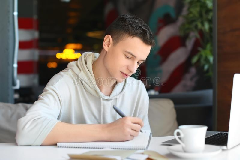 Young man writing letter at table in cafe. Mail delivery royalty free stock images