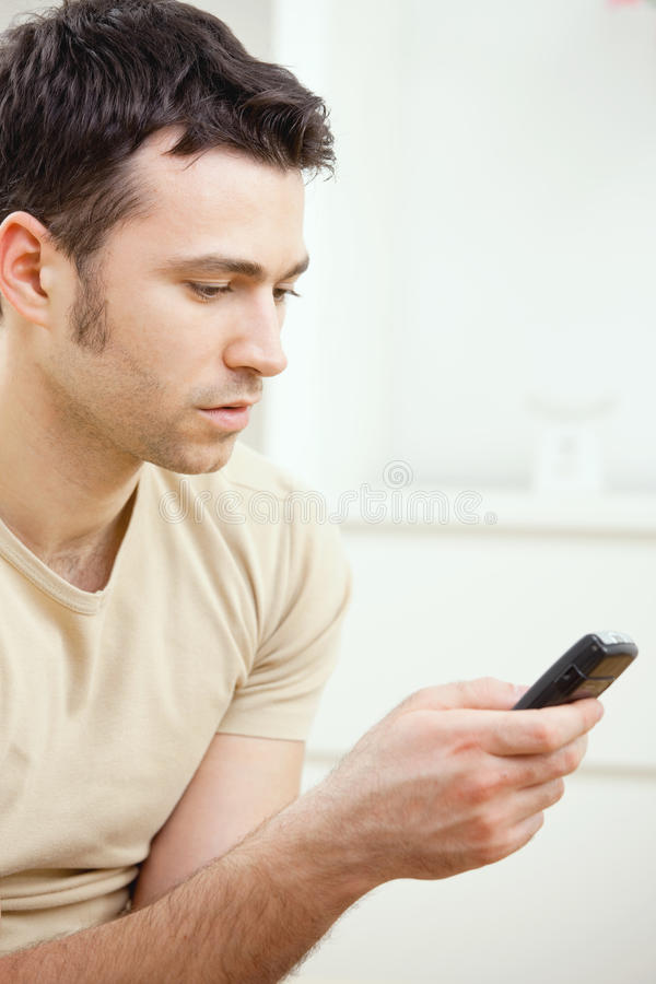 Young man writting SMS. Young handsome man writting SMS on mobile phone stock images