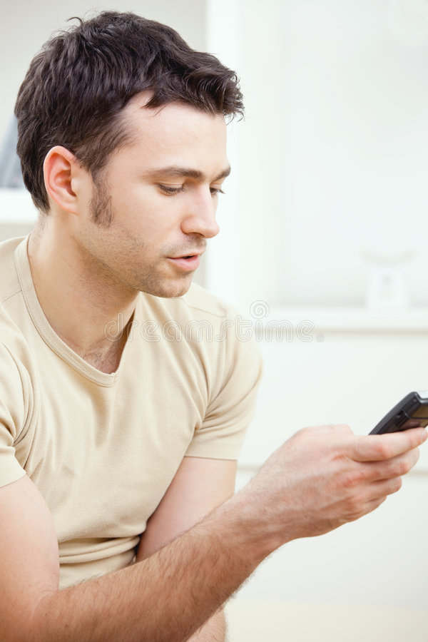 Download Young man writting SMS stock image. Image of interior - 9344805
