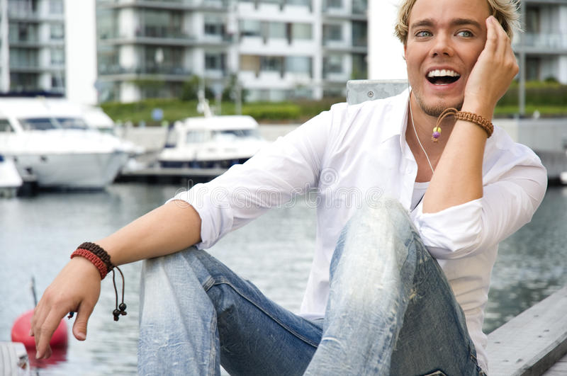 Young man at a yacht club. Young man sitting near some yachts at a yacht club listening to music stock photo