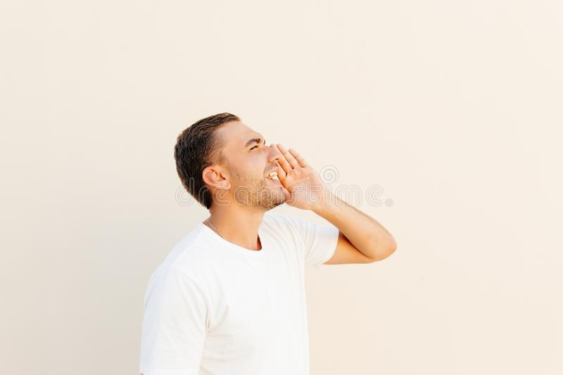 Young man putting hand around mouth yelling loudly on someone far on orange background. stock images