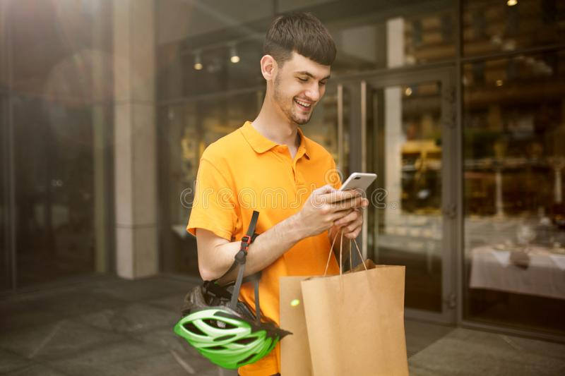 Young man as a courier delivering package using gadgets. Young man in yellow shirt delivering package using gadgets to track order at the city`s street. Courier stock photography