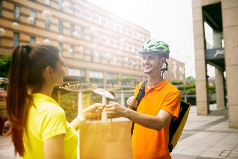 Young man as a courier delivering package using gadgets. Young men in yellow shirt delivering package using gadgets to track order at the city`s street. Courier royalty free stock photo