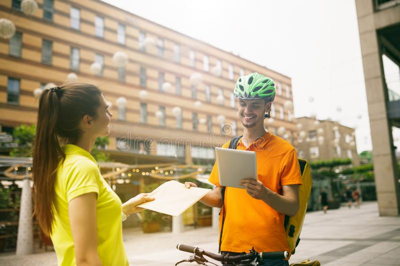 Young man as a courier delivering package using gadgets. Young men in yellow shirt delivering package using gadgets to track order at the city`s street. Courier royalty free stock photography