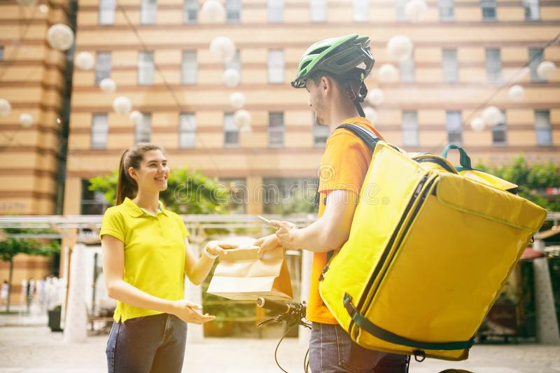 Young man as a courier delivering package using gadgets. Young men in yellow shirt delivering package using gadgets to track order at the city`s street. Courier royalty free stock images
