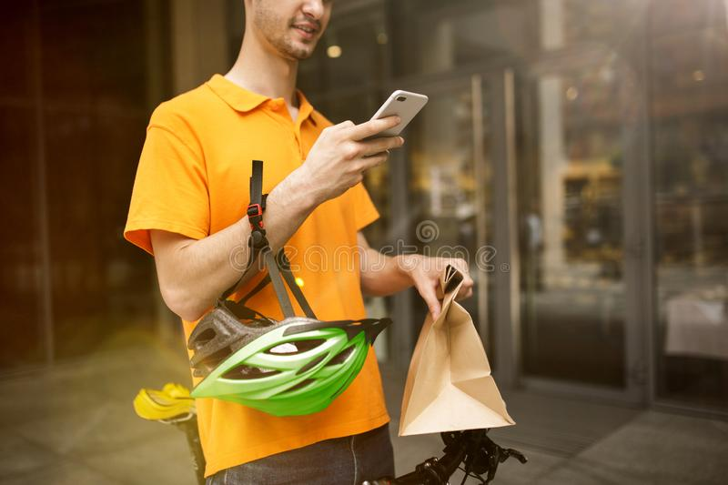 Young man as a courier delivering package using gadgets. Young man in yellow shirt delivering package using gadgets to track order at the city`s street. Courier royalty free stock photography