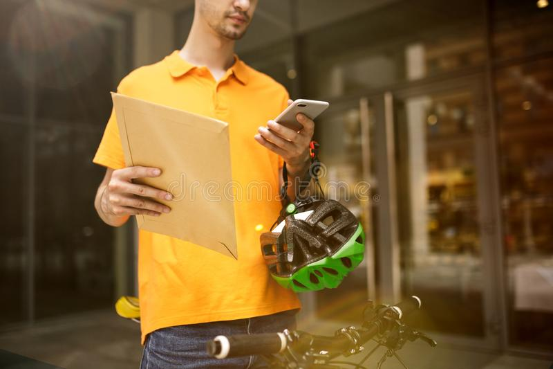 Young man as a courier delivering package using gadgets. Young man in yellow shirt delivering package using gadgets to track order at the city`s street. Courier royalty free stock photo