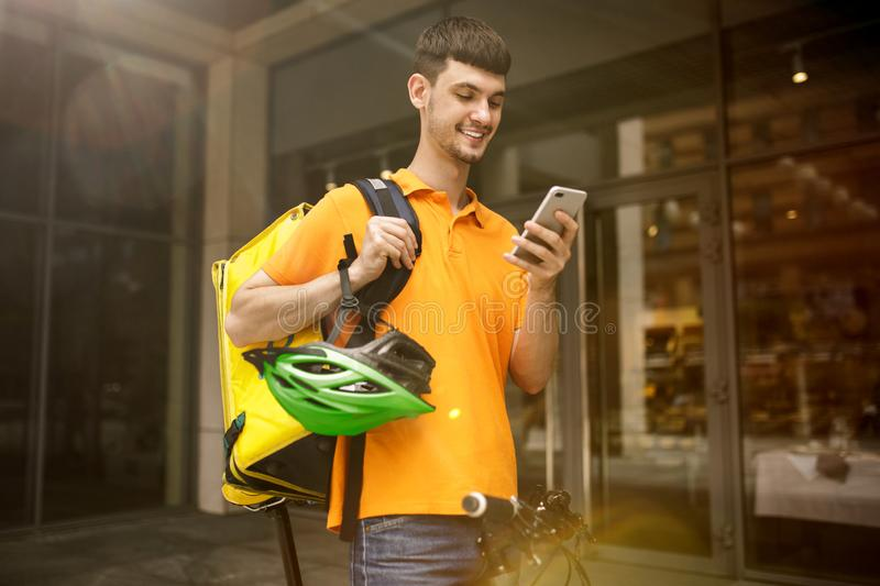Young man as a courier delivering package using gadgets. Young man in yellow shirt delivering package using gadgets to track order at the city`s street. Courier royalty free stock photos