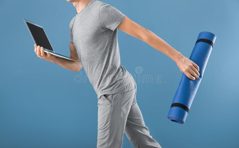 Young man with yoga mat and laptop running on color background. Concept of balance between rest and work royalty free stock photo