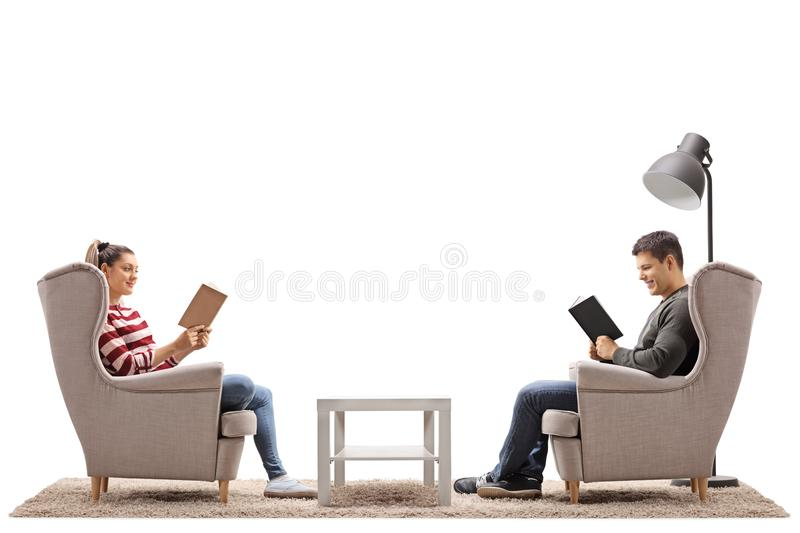 Young man and a young woman seated in armchairs reading books stock photos