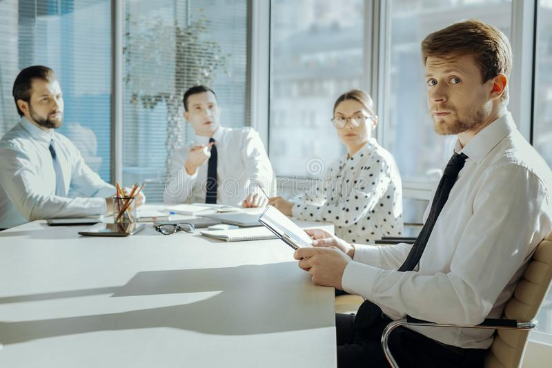 Young manager being nervous during meeting with bosses. Ready for scolding. Handsome young manager sitting at the meeting with the board of directors and looking royalty free stock images