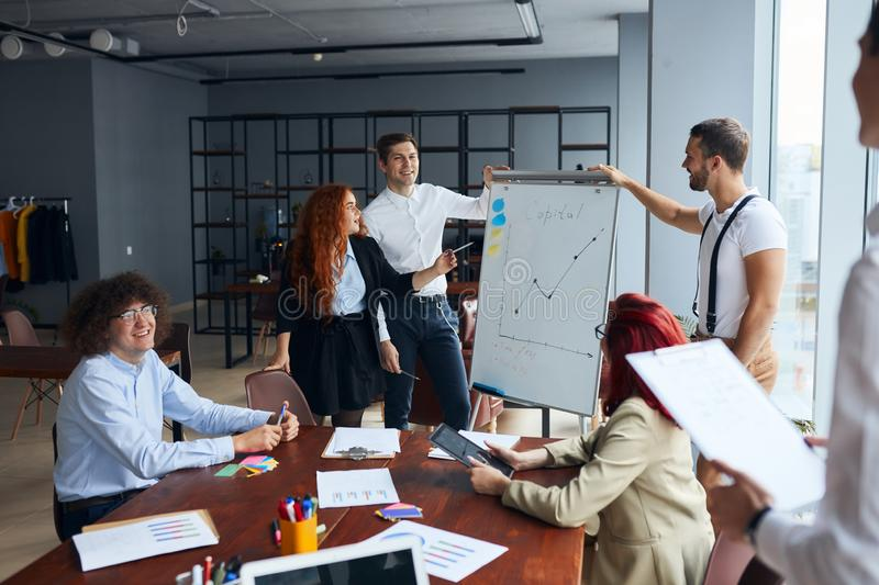 Young manager explaining business project on flip chart to coworker in modern office stock photos