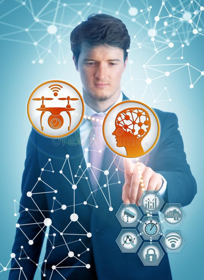 Young IT Manager Pairing AI And Smart Drone. Concentrated young IT manager pairing artificial intelligence and smart drone for real-time data processing in stock photos