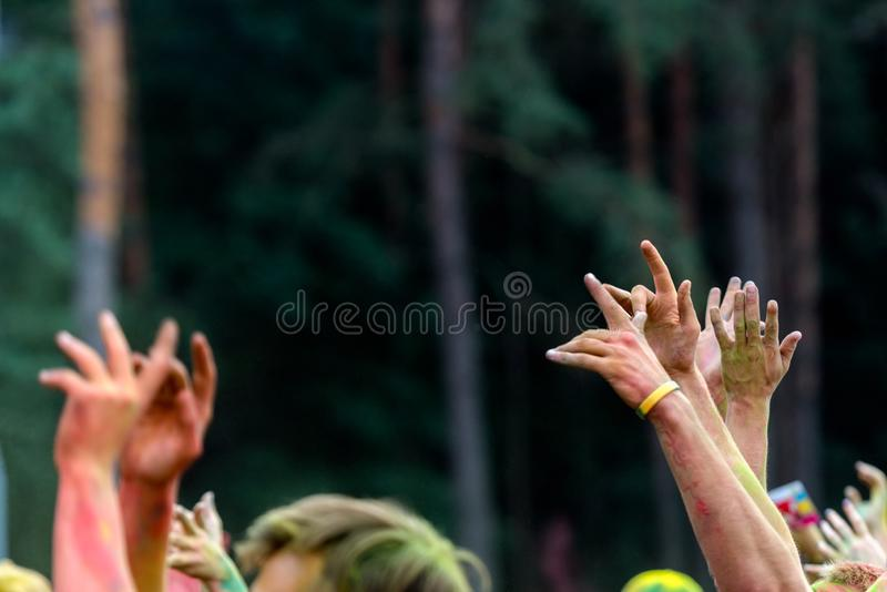 Young mans hands in the air in a color fest with yellow dust. Fun and joyful colour festival moment. Young people enjoying time. Together. Youth friendship stock images