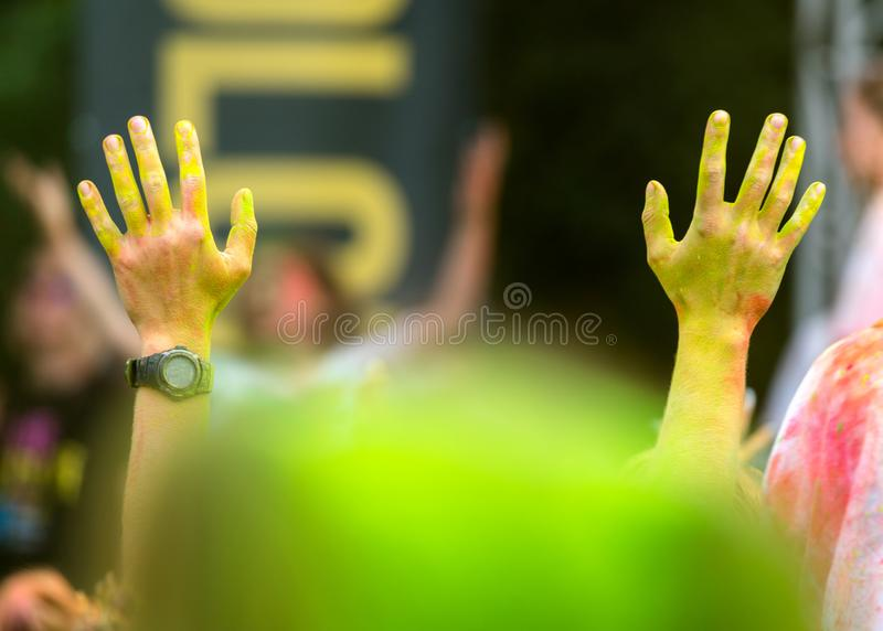 Young mans hands in the air in a color fest with yellow dust. Fun and joyful colour festival moment. Young people enjoying time. Together. Youth friendship royalty free stock photos