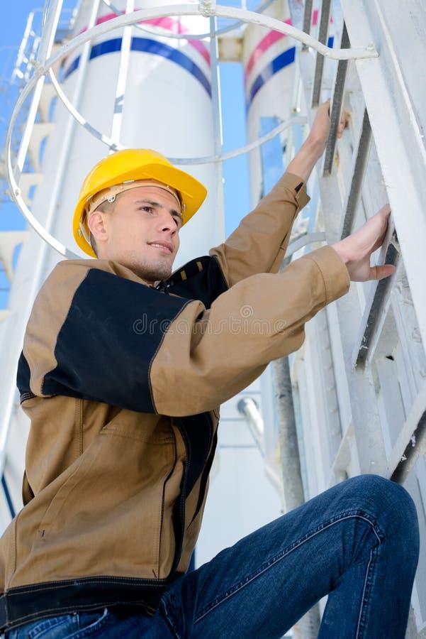 Young manual worker climbing enclosed metal ladder. Climb royalty free stock image
